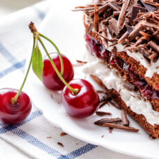 Black Forest cake piece on white plate with cherries berries close-up